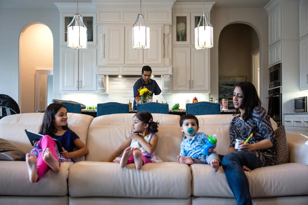 Khan prepares lunch while Ayesha and their children play on the couch.