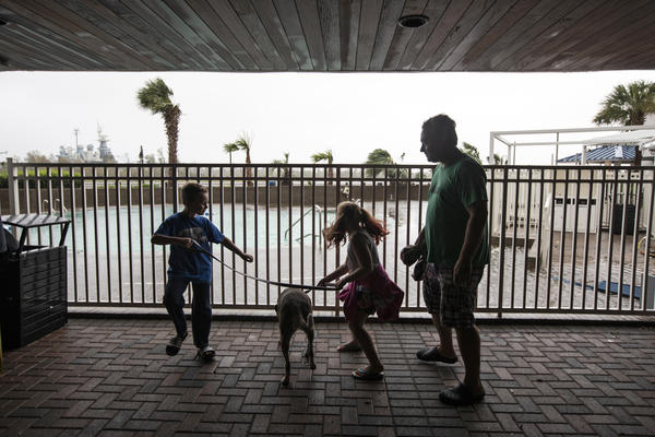 Reduced winds and rains gave Hopper Baumgardner (left) a chance to walk his dog, Dottie. He was joined by sister Maysie and father Matt at the Hotel Ballast in Wilmington, N.C., on Friday.