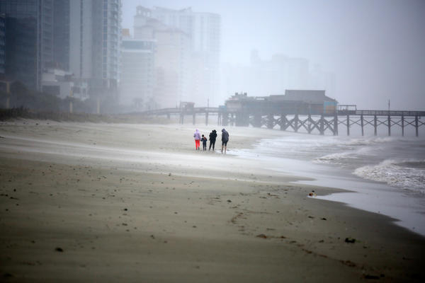 A handful of people walk along Myrtle Beach near Pier 14 in South Carolina. Electricity in the downtown area is out, and all businesses are closed.