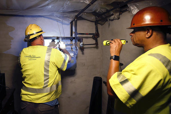 Columbia Gas employee Brian Jones shines a flashlight so his partner, using a wrench, can shut off the gas in a home Friday in Andover. (Winslow Townson/AP)