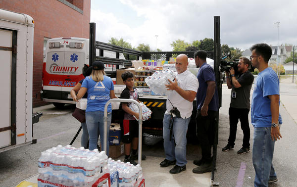 Volunteers help to unload a truck of donations outside the Parthum School in Lawrence Friday. (Mary Schwalm/AP)