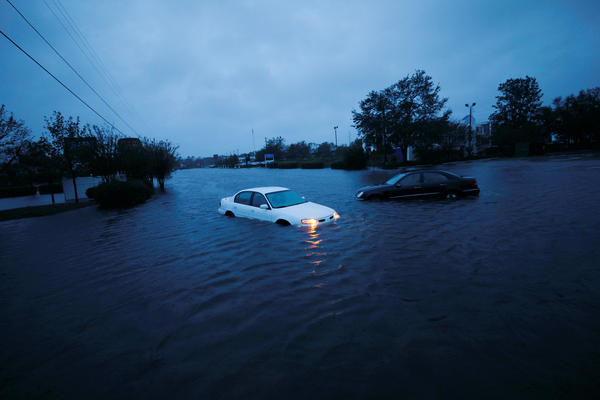 An abandoned car's hazard lights continue to flash as it sits submerged in rising floodwaters on Saturday morning in North Carolina.