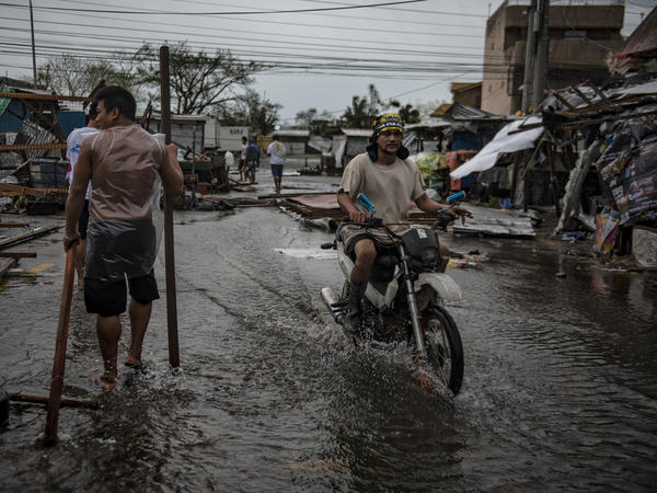 Residents walk on flooded streets as typhoon Mangkhut batters their city on Sept. 15 in Tuguegarao, Philippines. Typhoon Mangkhut battered northern Philippines as it made landfall Saturday morning leaving at least 12 people dead.