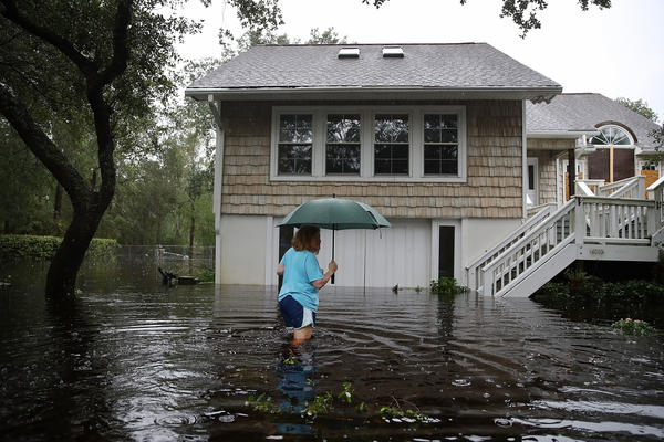 Kim Adams makes her way to her home that is surrounded by floodwaters on Saturday in Southport, N.C.