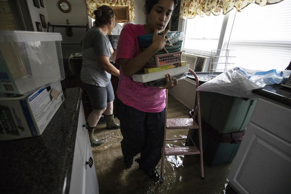 Michelle Mullins (left) collects her belongings with the help of her daughter-in-law, Stephanie Mullins, to save from mold and mildew in the house in Castle Hayne, N.C. This is the third time the home has flooded since they have lived there as a married couple but they did not renew the flood insurance because the FEMA premiums are too high.