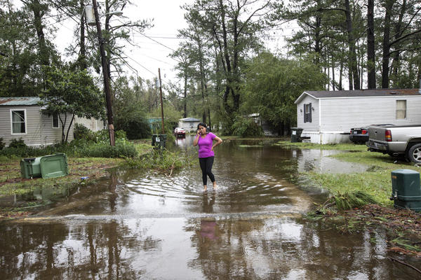 Gabriella Ortiz talks on the phone while walking in Castle Hayne, N.C., on Saturday. Surge and rain water from Florence continue to flood Northside Mobile Home Park. Fallen limbs and debris have cut off power and access.