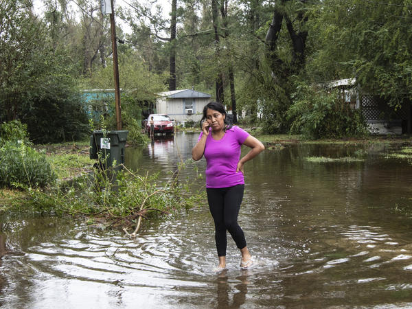 Gabriella Ortiz talks on the phone while walking in her neighborhood in Castle Hayne, N.C., on Saturday. Surge and rain water from Florence continue to flood Northside Mobile Home Park. Fallen limbs and debris have cut off power and access.