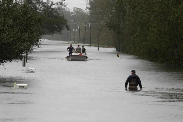 A member of the U.S. Coast Guard walks down Mill Creek Road Saturday checking houses after Florence hit Newport, N.C.