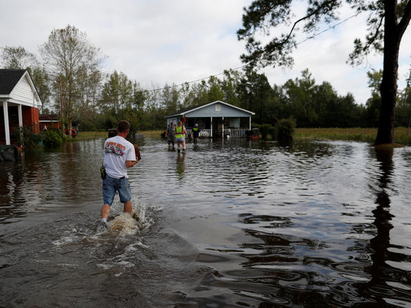 Members of the Marion Rural Fire Department hand-deliver supplies to a homeowner flooded by rains from Florence in Marion, S.C., on Monday.