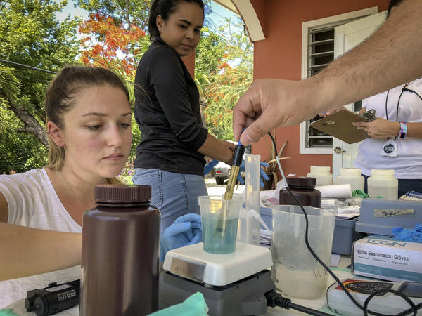 Graduate student Melanie Warren and laboratory technician Taina Rodriguez Curet work with Fernando Rosario-Ortiz to test tap water samples in Puerto Rico for lead. Initial results suggest potentially dangerous levels of lead in some drinking water that Rosario-Ortiz hopes to investigate further in larger studies.