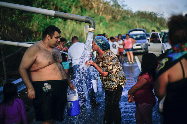 People who lost access to water in the wake of Hurricane Maria gather at pipes carrying water from a mountain creek, on the side of the road in Utuado, Puerto Rico, in October 2017.