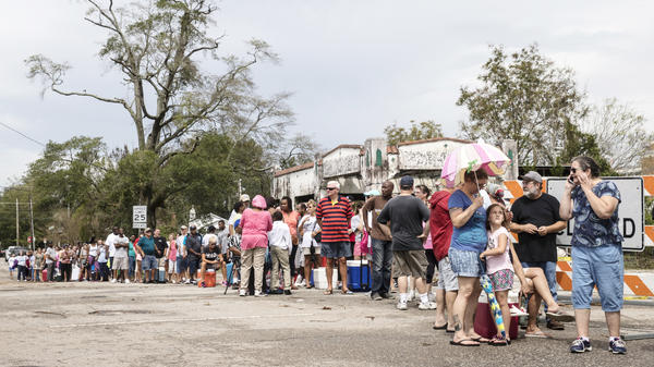 People wait in line for ice in Wilmington, N.C., on Monday.
