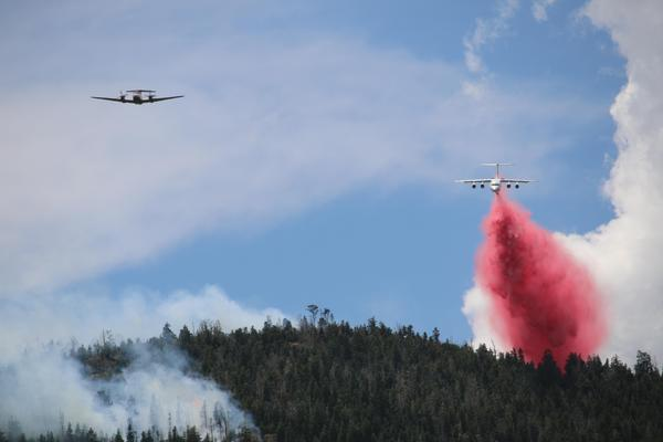 A lead plane, at left, shows the way for an air tanker dropping flame retardant on the Cove Creek Fire in Utah in July.
