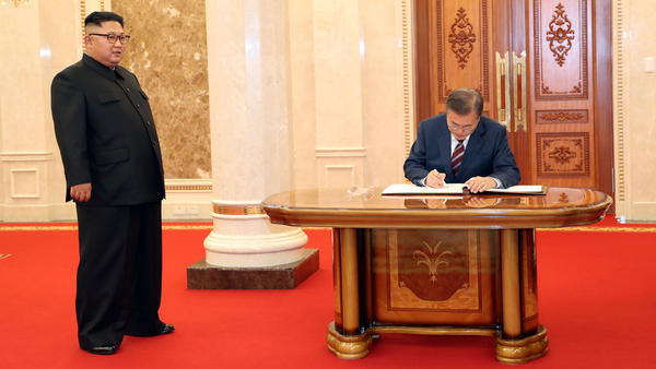 Signing in: South Korean President Moon Jae-in signs a guestbook as North Korean leader Kim Jong Un looks on at the headquarters of the Central Committee of the Workers' Party of Korea in Pyongyang, North Korea.