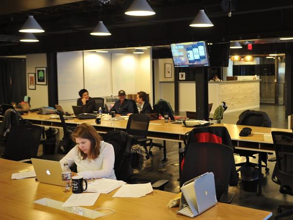 People work at tables inside the WeWork co-working space in Washington, D.C., in 2013. The company pioneered the office rental sector known as co-working, where users lease shared workspace by the month.