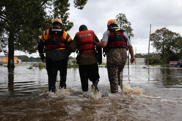 Lumberton Fire and Rescue members help a resident walk through flooded waters in Lumberton, N.C., on Monday.
