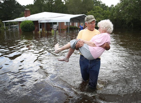 Bob Richling carries Iris Darden as water from the Little River starts to seep into her home in Spring Lake, N.C. on Monday.