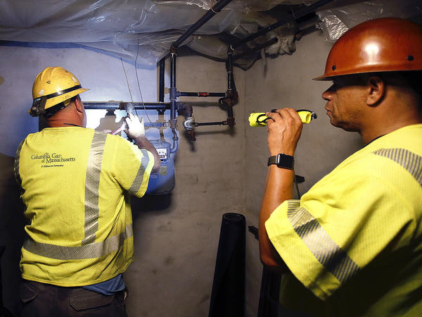 Columbia Gas employee Brian Jones shines a flashlight so his partner, can shut off the gas in a home on Sept. 14, in Andover, Mass. On Tuesday, lawyers filed a class action lawsuit on behalf of thousands of residents impacted by last Thursday's gas explosions and fires triggered by a problem with a gas line that feeds homes in several communities north of Boston.
