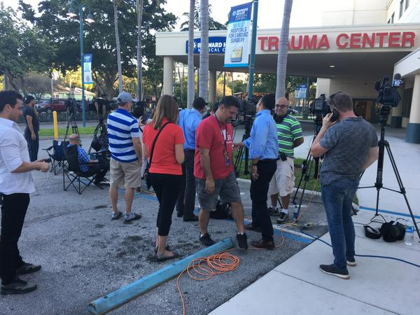 Reporters gather at a media staging area outside the hospital, waiting for updates about shooting victims.