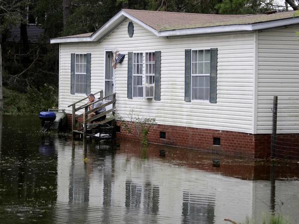 A North Carolina resident sits on his staircase earlier this week, staring into the water that surrounded his home after Florence hit Emerald Isle, N.C.