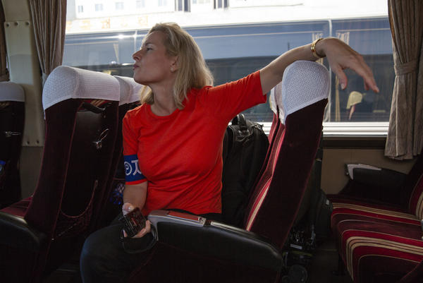<em>All Things Considered</em> host Mary Louise Kelly, wearing the government-mandated armband marking her as a foreign journalist, waits on a bus in Pyongyang.