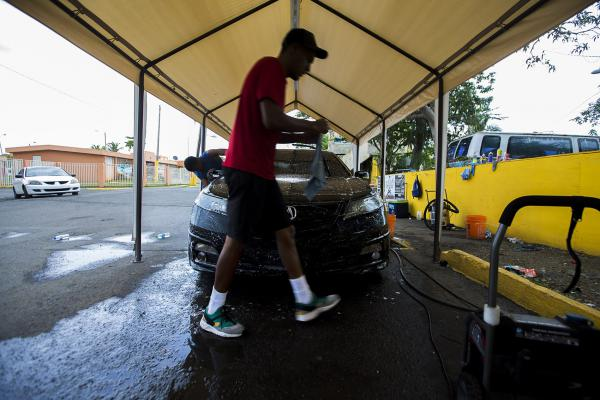 A worker at a pop-up car wash in Barrios-Bravos de Boston walks around a car he is cleaning. Several people lost their jobs after Hurricane Maria hit Puerto Rico.  Unemployment remains high on the island and many here are doing everything they can to make ends meet. The U.S. Department of Labor reports the unemployment rate on the island was 9.1% in July down from 11% in November. (Jesse Costa/WBUR)