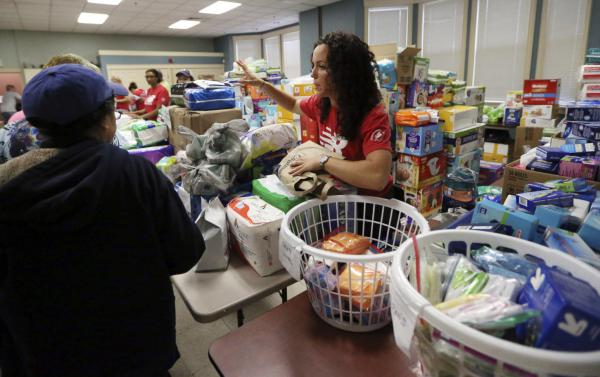 Volunteers at the Senior Center in Lawrence hand out food and supplies Tuesday, in the wake of last week's gas explosions and house fires in the Merrimack Valley. (Elise Amendola/AP)