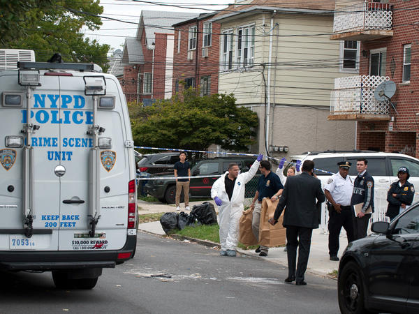 Police gather outside the private home where a day care center is located in the Queens borough of New York City on Friday, after three babies and two adults were stabbed there.
