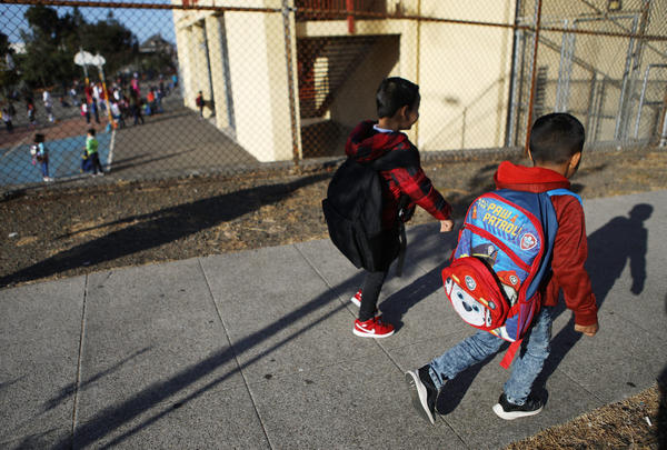 """Honduran 6-year-old Anthony (right) walks to school on Sept. 10, 2018 in Oakland, Calif. He and his father Juan fled their country, leaving many family members behind, and crossed the U.S. border in April at a lawful port of entry in Brownsville, Texas, seeking asylum. They were soon separated and spent the next 85 days apart in detention. Juan was sent to Tulsa, Oklahoma, while his son was sent to a detention shelter New York. They were one of almost 2,600 families separated due to the Trump administration's """"zero tolerance"""" immigration policy. (Mario Tama/Getty Images)"""