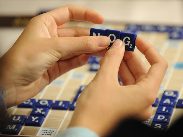 A competitor arranges letter tiles while competing in the 2008 National School Scrabble Championship, in Providence, R.I. On Monday, Merriam-Webster published a revised version of the<em> Official Scrabble Players Dictionary</em>, adding 300 new words.