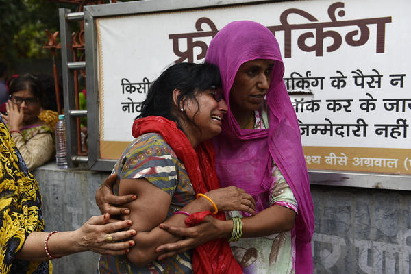 Relatives mourn before the funeral for family members who reportedly died by suicide at their home in Burari, India, this summer.