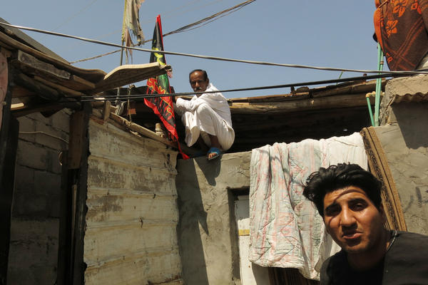 Ahmed Hussein (right) and his neighbor Kareen Khairala. Khairala is fixing a flag of Imam Hussein to the roof of his house in the al-Aleea neighborhood in Basra during the month of Muharram, when Shiite Muslims commemorate the battle of Karbala 14 centuries ago.