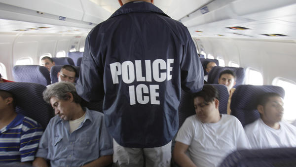 An Immigration and Customs Enforcement agent walks down the aisle among shackled Mexican immigrants on board a U.S. Immigration and Customs Enforcement charter jet for deportation.