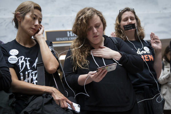 Protesters rallying against Kavanaugh watch testimony from Ford on a smartphone inside the Hart Senate Office Building in Washington, D.C.