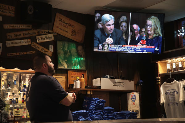 Adam Kruppa, bartender at the Billy Goat Tavern in Chicago, watches the testimony on a television at the bar.