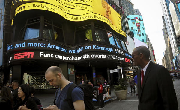A news ticker in New York City's Times Square shows headlines about the Senate Judiciary Committee hearings.