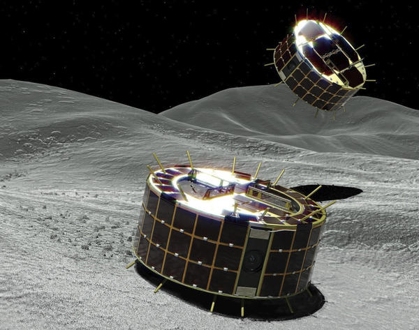 A computer graphic image provided by Japan's space agency shows two drum-shaped and solar-powered rovers on an asteroid. A Japanese unmanned spacecraft released two small rovers on the asteroid Ryugu last week.