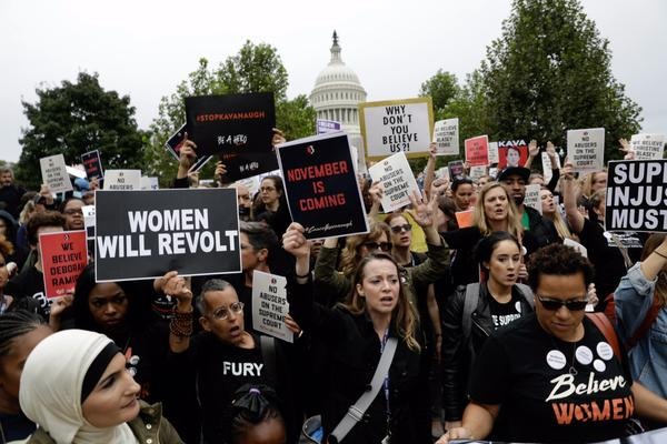 Protesters rally against Supreme Court nominee Brett Kavanaugh as they march near the Capitol.