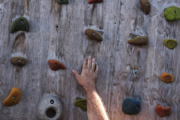 Skelton touches the bouldering wall in the backyard of his home. He co-founded an organization called Paradox Sports to give other veterans adaptive climbing experiences.