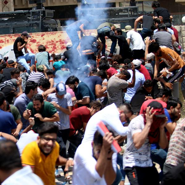 Protesters duck as Iraqi security forces fire tear gas during a demonstration against unemployment and a lack of basic services in Basra.