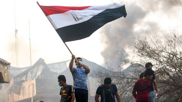 An Iraqi protester waves a national flag while demonstrating outside the burned-down local government headquarters in the southern city of Basra on Sept. 7, during demonstrations over problems including poor public services.