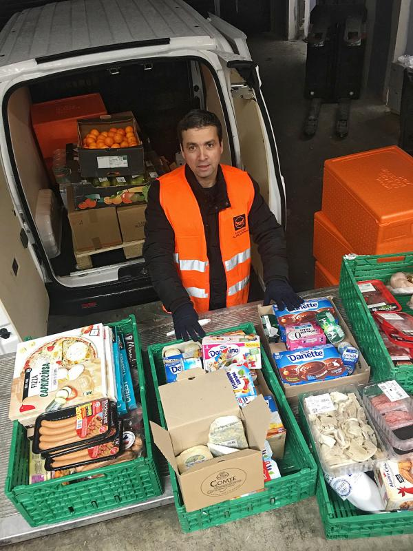 Djerbrani checks food donations from a French grocery store before driving it across town to a church, which will distribute it to poor families.