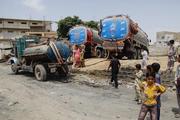 A large water tanker in the Orangi slum in Karachi transfers part of its water to a smaller tanker. The area doesn't have running water, and the streets are too narrow for large water tankers, so residents move the water to smaller tankers that can ply the hilly area.