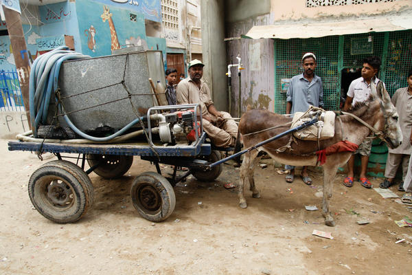 A man delivers a small tanker of water lashed to his donkey cart in the Korangi slum in Karachi.