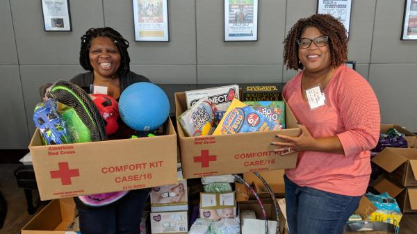 Krista Holland (right) and Regina Wooten, another Wilmington principal, pose with toys Holland brought to a Chapel Hill shelter.