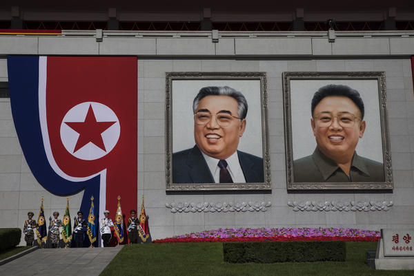 Military officials await the start of a military parade at Kim Il Sung Square. There was once only a portrait of the country's founder, Kim Il Sung (left), at the square. The portrait of his son and successor, Kim Jong Il, was added after the younger Kim's death in 2011.