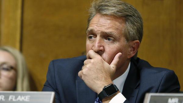 Sen. Jeff Flake, R-Ariz., listens as Christine Blasey Ford testifies before the Senate Judiciary Committee on Thursday.