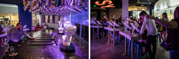 Left: A man picks up a drink crafted by a robot arm at Tipsy Robot in Las Vegas. Right: People watch robot arms craft drinks as others place their orders on an app.