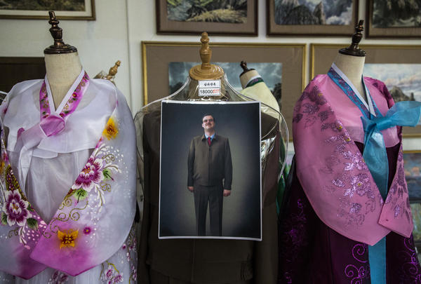At a souvenir store in Pyongyang, a foreigner serves as the model for a North Korean suit. Souvenir shops serve as a source of hard currency by selling expensive art, clothing, food and other souvenirs to tourists.<em> </em>