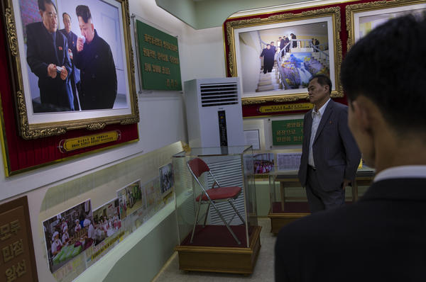 Many places in North Korea commemorate the visits of a leader with portraits, photos and other relics. At this cosmetics factory in Pyongyang, a set of rooms is dedicated to visits by all three leaders of North Korea: Kim Il Sung, Kim Jong Il and current leader Kim Jong Un. Here, a folding chair used by Kim Jong Un is displayed under a glass case.